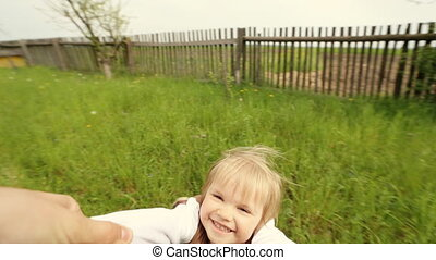 Dad holding hands of his dauther while flailing her on the...
