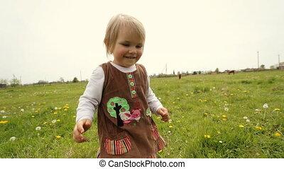 Cute little girl smile while running on the garden.