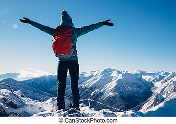 Hiker woman standing with hands up achieving the top,...