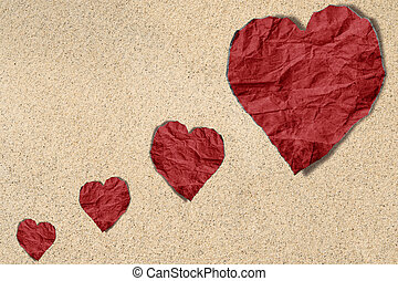 Red heart crumpled paper on sand