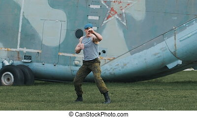 Soldier trains fighting skills. He performs a series of punching and kicking.