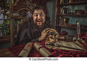 Smiling medieval fat monk in sitting in the dark room. -...