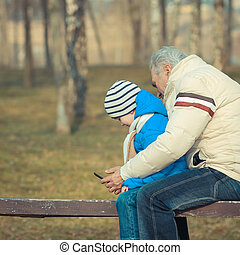 Grandfather and grandson are looking tablet on bench...