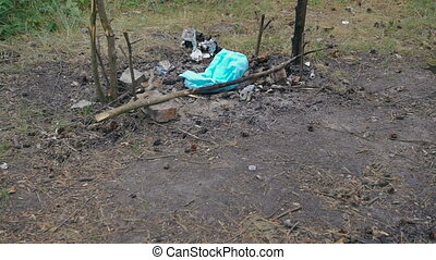 A campfire remains after picnic in green forest in full HD