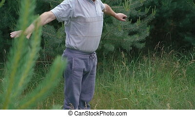 Old man does morning exercises squats up-down in the green...