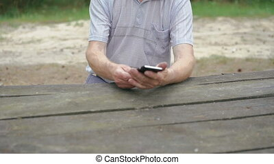 The old man with wrinkles uses the phone in the forest in...