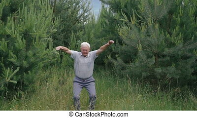 Old man does morning exercises squats up-down on the camera...
