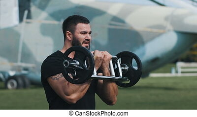 Strength training at a military base. Muscular man raises...