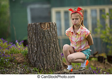 Little girl in a bad mood sitting near the house in the...