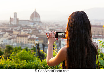 Teen in Florence takes a picture at the panorama. - Young...