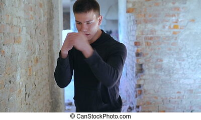 Kickboxer shadow boxing as exercise for the big fight in old building. Slowly