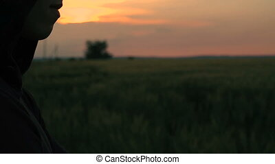 Profile of man in hood on the sunset in the field background...