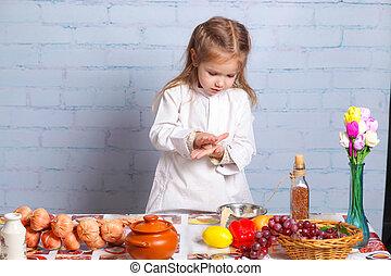 Little girl preparing dough for bread. Cute little girl in...