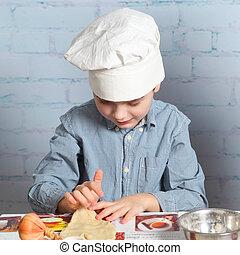 Little boy preparing dough for bread. Cute little boy in the...