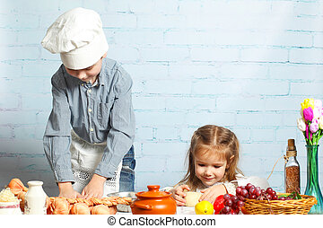 Children chefs. little brother and sister cook in the...