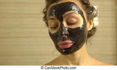 Pretty girl with cosmetic black face pack on her face. 4K...