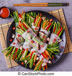 Spring rolls with vegetables and shiitake mushrooms on a...