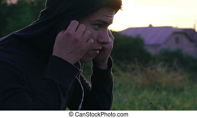 Happy young man listening to the music in earphones on the nature