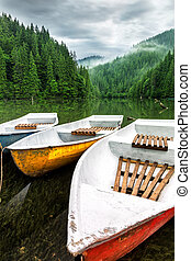 Mountain lake boats on cloudy day