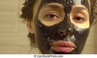 Beautiful young woman with cosmetic black face pack on her...