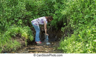 Spring - The woman takes water from a spring