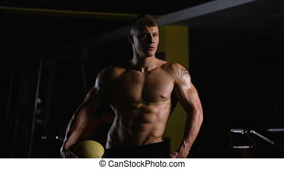 Bodybuilder on top form. Beautiful young athlete posing for a photo session