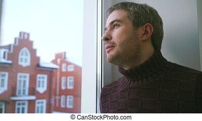 Handsome man in sweater looking through the window and smiling