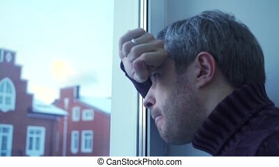 Troubled young man with grey hair looking through the window...