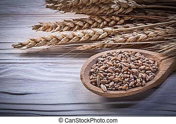 Wheat rye ears corn wooden spoon on wood board