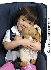Car Seat 004 - A young girl strapped into a car seat hold...