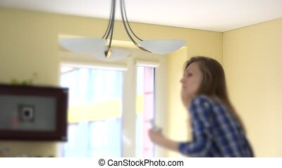 woman screw eco light bulbs in chandelier. - Worried girl...
