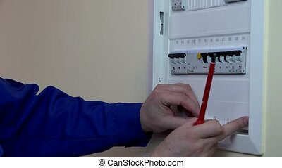 Skilled man hands repairing a circuit breaker. Static...
