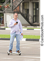 Business man riding an electronic scooter outdoors -...