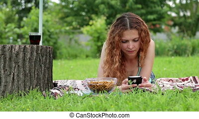 Young woman using mobile phone and lying on the green grass