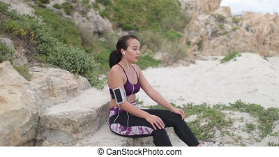 Young fit sports woman resting after workout on the beach....