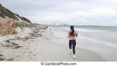 Young fit sports woman jogging on the beach. Super slow...