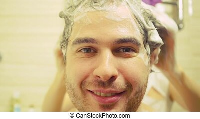 Cheerful man having his hair washed by young woman, close up...