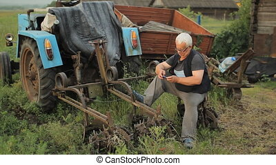 A man calling on the phone near the tractor. Agriculture surrounds
