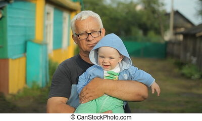 Grandfather holding his grandson in his arms. Beautiful baby...
