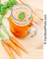 Glasses of carrot juice with carrot roots on wooden...