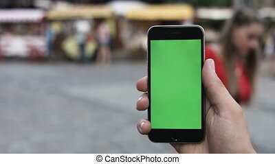 Close-up of male hands using smartphone outdoors in the city...