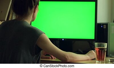 Over the shoulder shot of woman typing on a computer green...