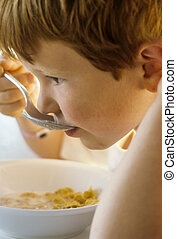 cute young boy has his breakfast with corn flakes and mild