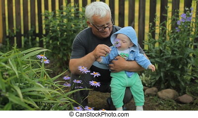 Grandfather giving a flower to his grandson Beautiful baby...