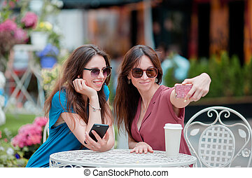 Two young girls taking selfie with smart phone at the...