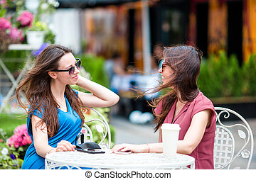 Two young girls at the outdoors cafe Two women after...