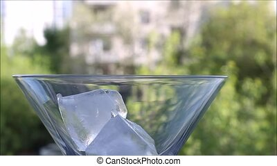 ice cubes appear one after another in a martini glass