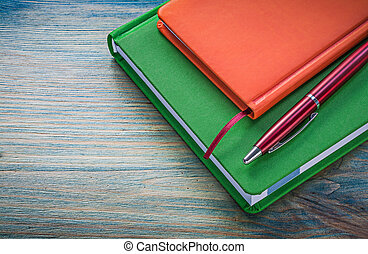 Assortment of notepads biro pen on wooden board office...