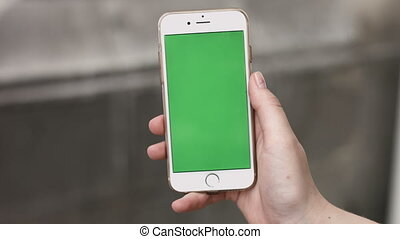 4K Close up of hand holding a smartphone with green screen...