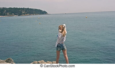 Young beautiful fashion model woman raises her arms up on the beach